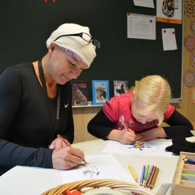 Satu Partanen tecknar med barn i gammelbacka skola.