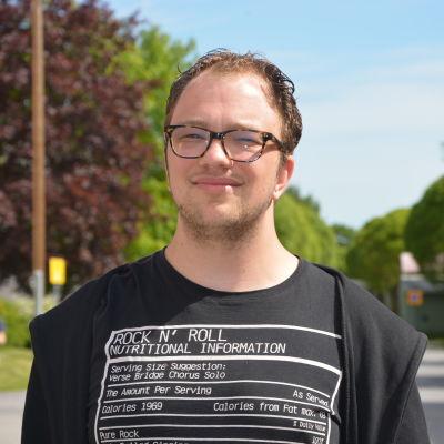 En porträttbild av Anton Plogman tagen utomhus i solsken. Han bär glasögon med sköldpaddsskalsfärgade bågar och en svart t-skjorta.