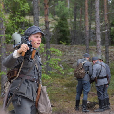 Määttä (David Sandqvist) med ett vapen på axeln i pjäsen Okänd soldat i Harparskog.