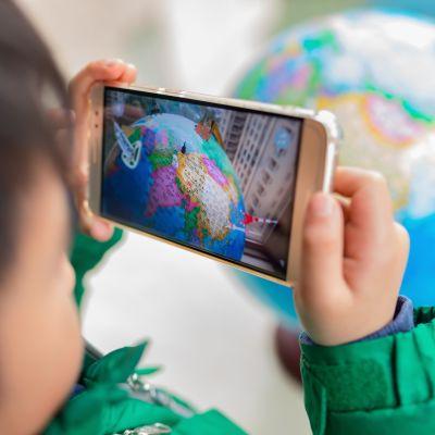 Kameran fokuserar på en mobilskärm som visar ett spel med en jordglob. I förgrunden ser vi ett suddigt barn som håller i mobilen.