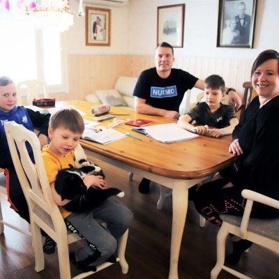 Ylisen perhe pöydän ääressä istumassa