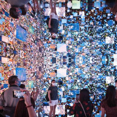 Ett sammelsurium av människor och bilder på en mässa för digital konst.
