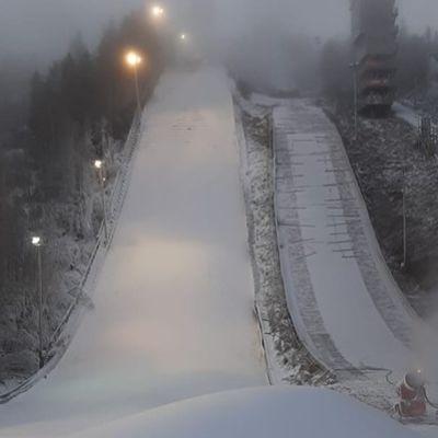 Lumitykki tekee lunta Ounasvaaran hyppyrimäelle.