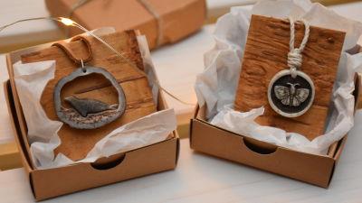 Två smycken gjorda av materialet horn. Det ena föreställer en säl, det andra en fjäril.