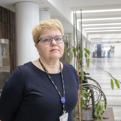 Kvinna klädd i mörkblå blus ser in i kameran. I bakgrunden sjukhusmiljö.