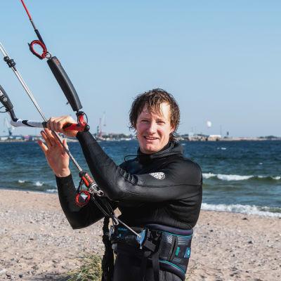 Leijalautailija Mikael Hyryläinen seisoo Tulliniemen rannalla Hangossa ja pitää kiinni leijastaan.