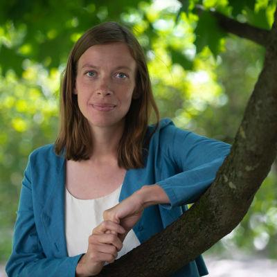 Li Andersson nojaa puistossa puun oksaan.