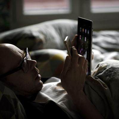 Mies katsoo puhelinta ja padia vuoteessa.