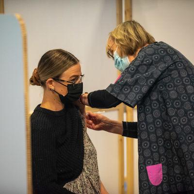Sairaanhoitaja pistää koronarokotteen potilaalle Energia Areenalla Vantaalla.