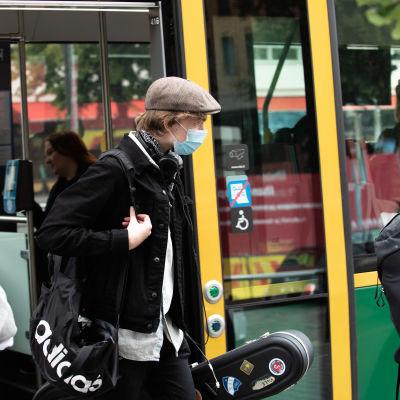 En man stiger av en spårvagn iklädd ansiktsskydd.