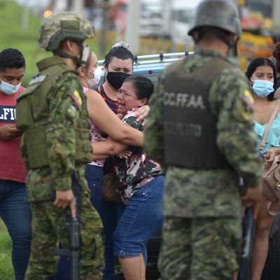 Itkevät naiset halaavat toisiaan, edessä sotilaita