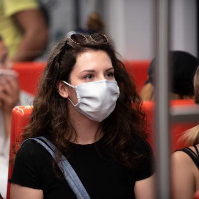 Nainen istuu metrossa maski päässään.