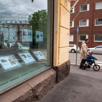 Ett skyltfönster med bostadsannonser. I bakgrunden ses en man som håller handen på ett cyklande barns axel.
