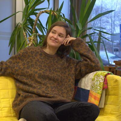 Maria Sann sitter på en gul soffa.