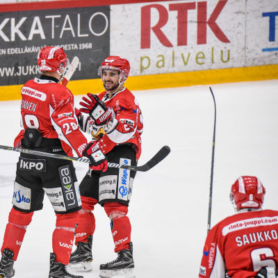 Rödklädda ishockeyspelare firar mål.