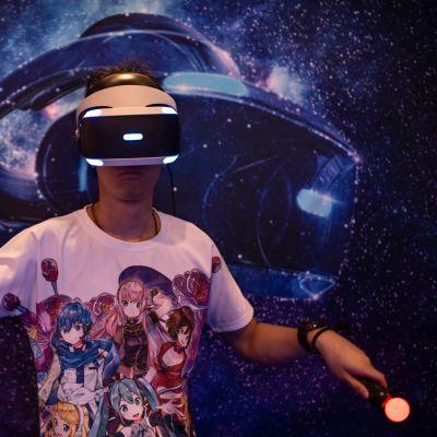 En man med VR-glas och kontroller i händerna ses spela ett spel. Han har på sig en t-shirt med anime-figurer.