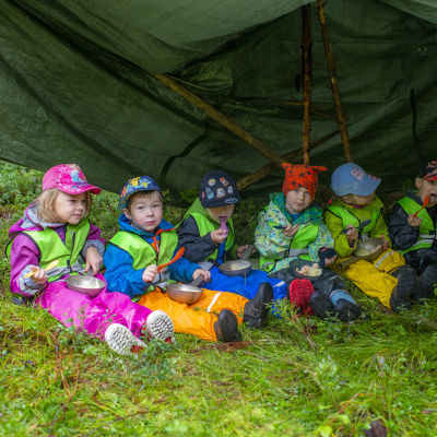 lapset ruokailee teltassa