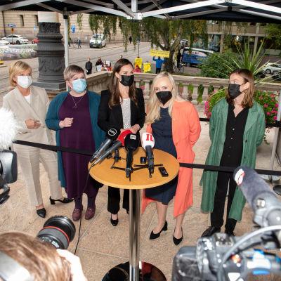 Partiledarna i Sanna Marins regering står bakom ett runt bord fyllt med mikrofoner och fotograferas.