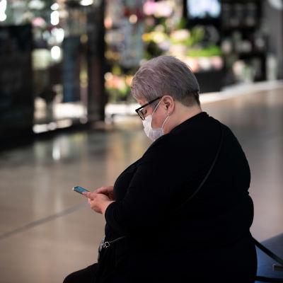 Nainen selaa puhelinta kauppakeskus Triplassa kasvomaski päässään.