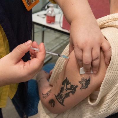 Sairaanhoitaja pistää koronarokotteen potilaalle Helsingin Messukeskuksessa.