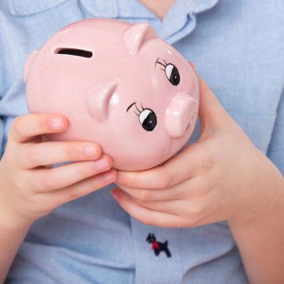 spargris i handen på en  liten flicka. symbolbild.