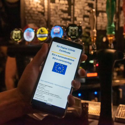 En mobiltelefon där man kan se EU:s digitala coronapass.