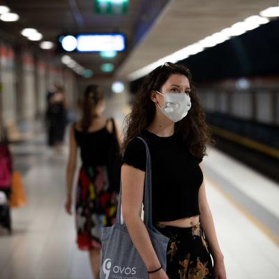 En kvinna som väntar på metron vid perrongen och bär munskydd.