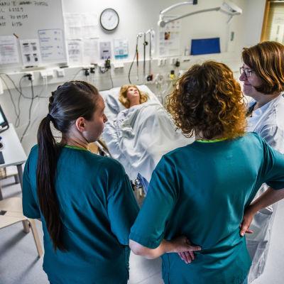 Tre sjukvårdare tittar på en patientsäng.