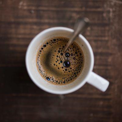 En mugg svart kaffe med en sked i.