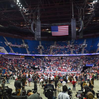 Donald Trump puhuu taustallaan suuri määrä tyhjiä istumapaikkoja. Etualalla suuri ihmisjoukko.