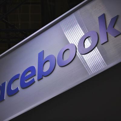 Skylt med texten Facebook i blått mot en vit bakgrund.