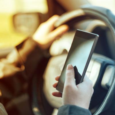 En person knappar på en smarttelefon i förarsätet på en bil.