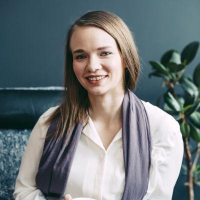 Saga Nyrén sitter i en stol med en kaffekopp i handen. Hon ser in i kameran och ler. Hon har på sig en vit skjorta, och en lila halsduk.