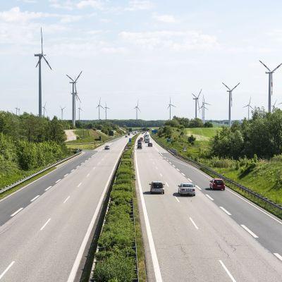 Bilar som kör på tyska motorvägen Autobahn A20 med vindkraftverk i bakgrunden.