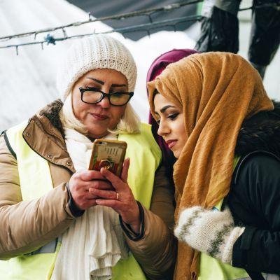 en blond kvinna och en kvinna i slöja tittar på en telefon