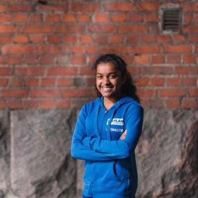 Tyttö seisoo  talon seinän vieressä ja hymilee
