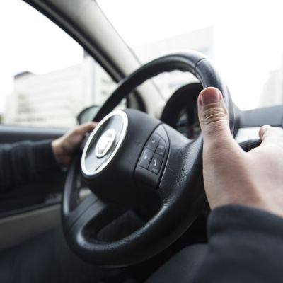 Kädet auton ratilla.