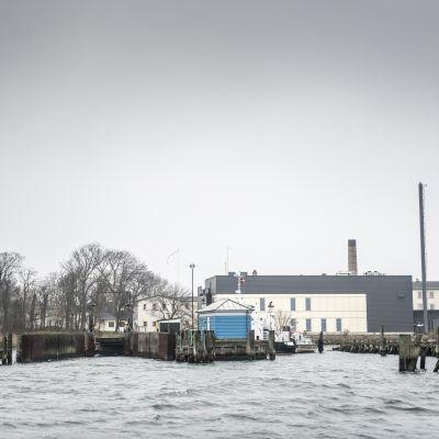 Ön Lindholm i Danmark sedd från havet, med byggnader och bryggor.