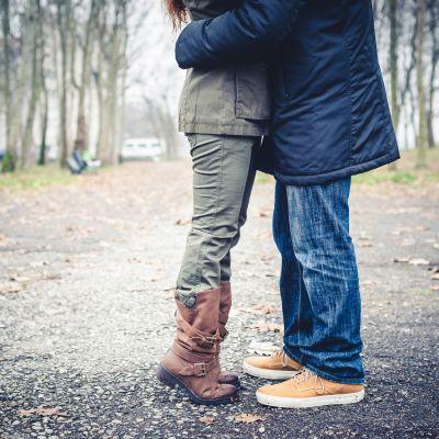 Benen på en man och en kvinna står mot varann ute i en park och kysser varann