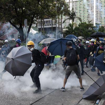 Demonstranter i Hongkong skyddar sig från polisens tårgaspatroner med paraplyn.