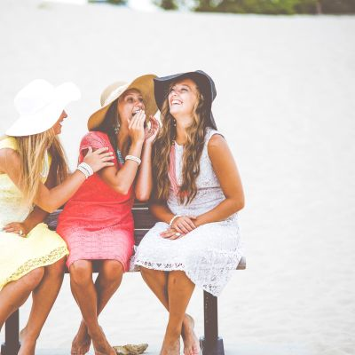 Kolme naista istuu yhdessä nauramassa.