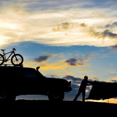 Pilvinen taivas ja silhuettina näkyvä jeeppi, polkupyörä ja teltta