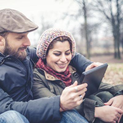 Man och kvinna sitter ute på marken och tittar på en tablett