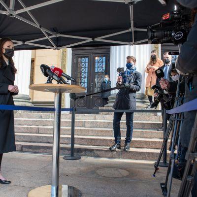 Statsminister Marin i helfigur möter pressen utanför Ständerhuset.