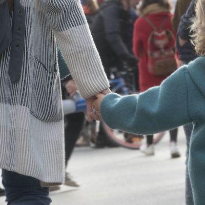 Mamma och barn som håller hand fotograferade bakifrån med människor i bakgrunden.