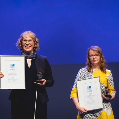 Heidi Hannus (vas.) ja Marika Konga seisovat kehystetyn palkinnon kanssa.