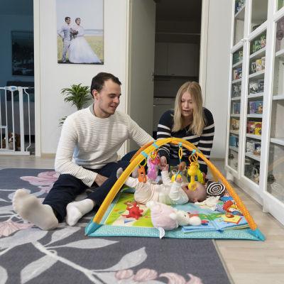 Mies ja nainen leikkivät lapsen kanssa.