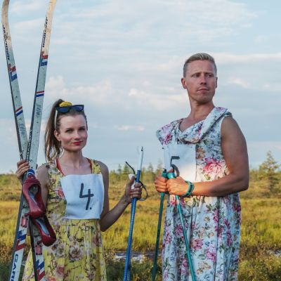 Egenlandin juontajat Hannamari Hoikkala ja Nicke Aldén seisovat suolla kukkumekot yllään ja sukset ja sauvat käsissään.