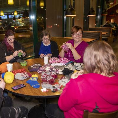 Neuleryhmä kutoo villasukkia pyöreän pöydän ääressä huoltoasemalla