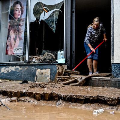 En kvinna städar ingången till en affär som skadats ordentligt i stormen i Tyskland